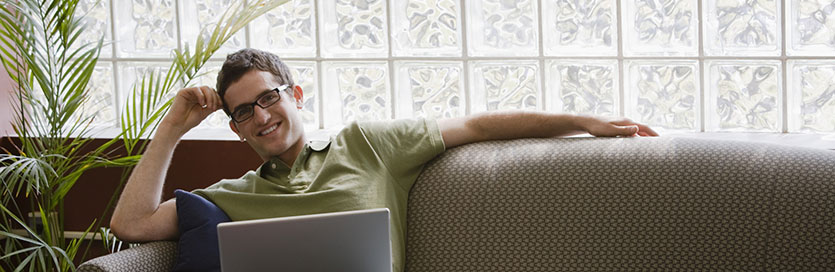 Young man sitting on couch using a laptop.